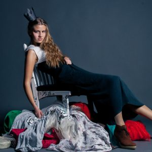 sitting on a pile of clothes as the queen of consumerism